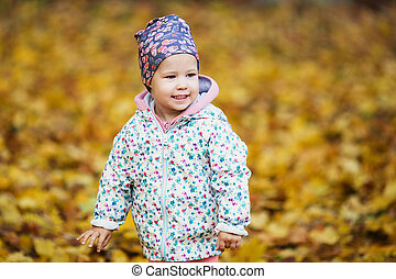 Cute baby girl among the golden autumn maple leaves