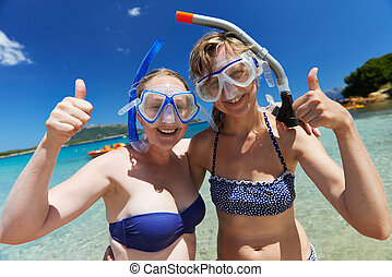 two smiling happy women friends in snorkeling mask with tube on the turquoise sea beach