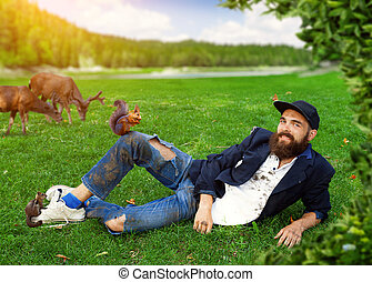 Happy vagrant lying on the lawn with animals