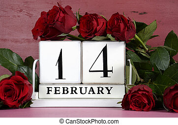 Happy Valentine Day vintage wood calendar for February 14 on red and pink vintage wood background with bouquet of red roses, closeup.