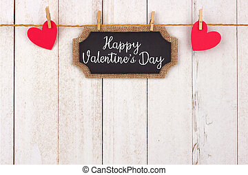 Happy Valentines Day chalkboard gift tag and hearts hanging from line, top border against white wood