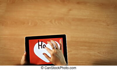 Happy valentines day. Female writing inside white heart on tablet, love calligraphy
