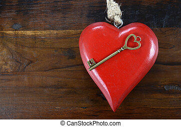 Happy Valentines Day key to my heart concept with large hanging heart on dark wood background.