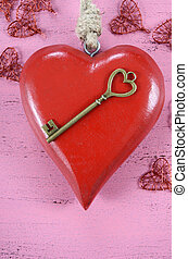 Happy Valentines Day key to my heart concept with large hanging heart on shabby chic pink wood background.