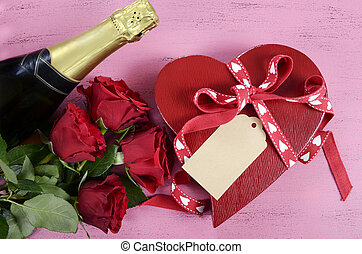 Happy Valentines Day red heart shape gift box with bottle of champagne and red roses on shabby chic vintage style pink wood table background.