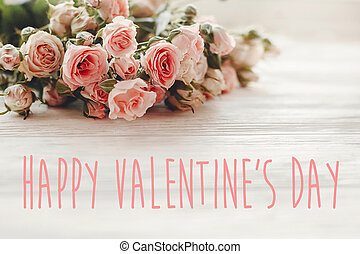 Happy Valentine's Day text sign on pink small roses on wooden background in light. Tender Flowers image. Valentines day floral greeting card.