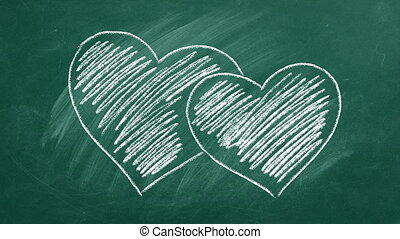 Two hearts are hand drawn with chalk on a greenboard. Valentines day. Love concept. I Love You