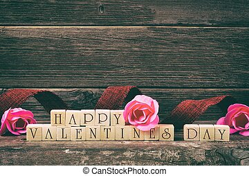 Happy Valentines Day wooden blocks with ribbon and roses against a rustic wood background, vintage styling