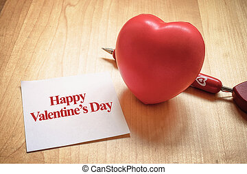 Happy Valentines day word on note paper with red heart and pen on wood table, Love concept