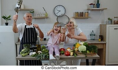 Happy vegan senior couple dancing with granddaughter child while cooking vegetables in kitchen