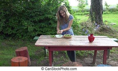 happy vegetarian woman hands husk fresh green peas on red wooden table. 4K