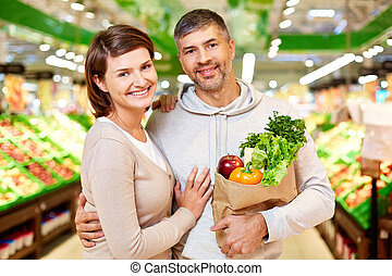Happy vegetarians - Image of happy couple with paperbag full...
