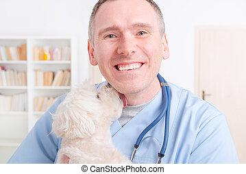 Happy vet holding a little dog