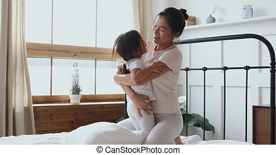 Happy vietnamese mother and child daughter play laugh in bed...