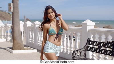 Happy vivacious trendy woman in skimpy summer shorts and...