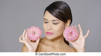 Happy vivacious woman holding two pink donuts - Happy...