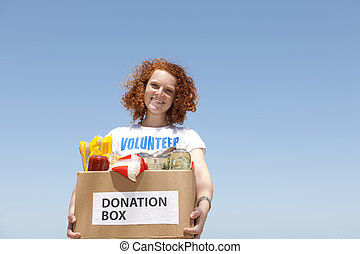 happy volunteer carrying food donation box