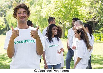 Happy volunteer gesturing thumbs up - Portrait of happy ...