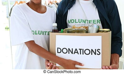 Happy volunteer team holding a donation box