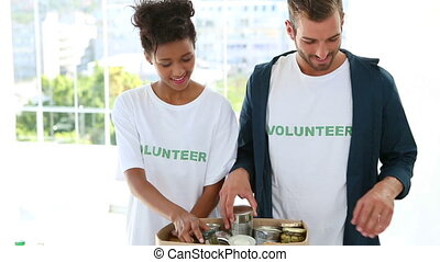 Happy volunteer team packing a food donation box and smiling at camera