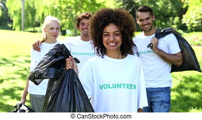 Happy volunteers picking up trash in the park on a sunny day