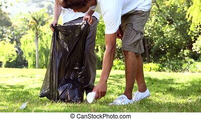 Happy volunteers picking up trash - Happy volunteers picking...