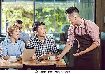 Happy waiter serving couple