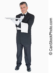Happy waiter with silver tray and towel
