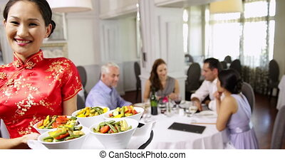Happy waitress presenting tray with vegetables