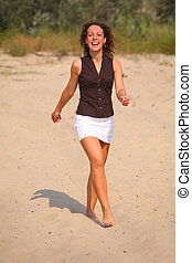 happy walking woman on sand
