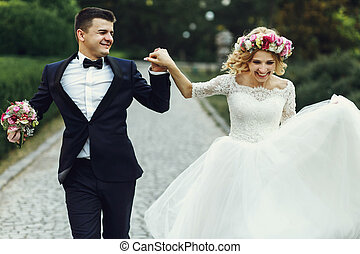 Happy wedding couple charming groom and blonde bride dancing in park
