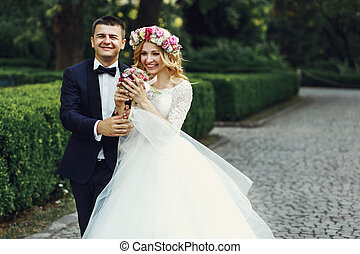 Happy wedding couple charming groom and blonde bride laughing in park