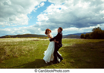 Happy wedding couple dance on the hill under a deep blye sky