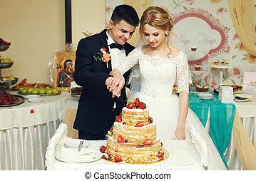 Happy wedding couple handsome groom and blonde bride carving delicious wedding cake