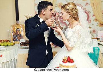 Happy wedding couple handsome groom and blonde bride eating delicious wedding cake