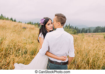 Happy wedding couple hug in the field. Sunny day at mountains