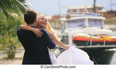 Happy wedding couple hugging and twisting at the berth in Montenegro, Budva