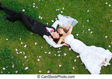 Happy wedding couple lying on green grass