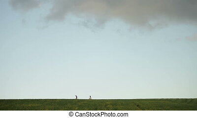 Happy wedding couple running skipping on the green field. Beautiful skyline on background.