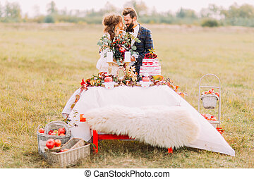 Happy wedding couple sitting at holiday table in the field