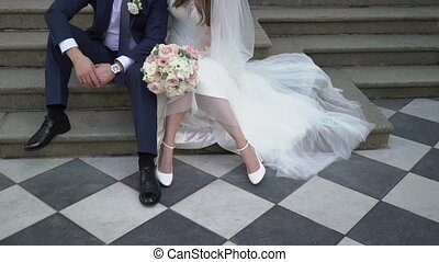 Happy wedding couple sitting on stairs outdoors