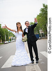 happy wedding couple standing for a road and wave hands