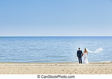 happy wedding couple standing on beach