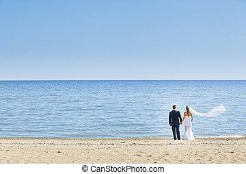 happy wedding couple standing on beach