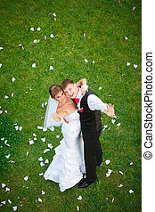 Happy wedding couple standing on green grass