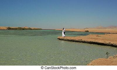 Happy wedding couple standing on the beach. Honeymoon in Egypt