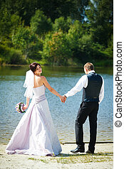 Happy wedding couple stands in the ray of sun on the lake shore