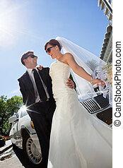 Happy Wedding Couple with Limo