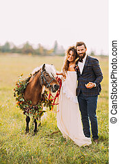 Happy wedding couple with pony smiling on the field.