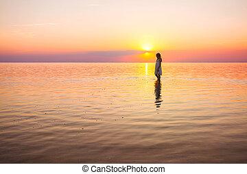 little girl looks at the sunset